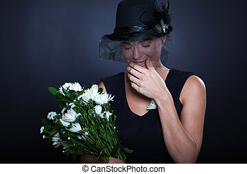 sad widow crying at funeral - sad widow with mourning...