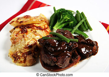Beef tournedos dinner - A meal of beef tournedos on a...
