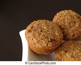 Cranberry Bran Muffins sitting on a white plate with a dark...