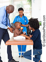 pediatrician examining baby boy - male african american...