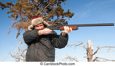 hunter aiming - Male hunter in a red hat aims his gun