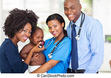 african pediatricians with mother and baby after checkup -...