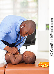 african doctor examining baby boy in his office
