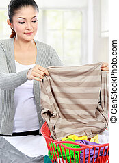 laundry at home - beautiful woman doing the laundry at home