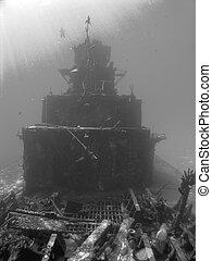 Scuba Diver descends on a Sunken Ship in Black and White