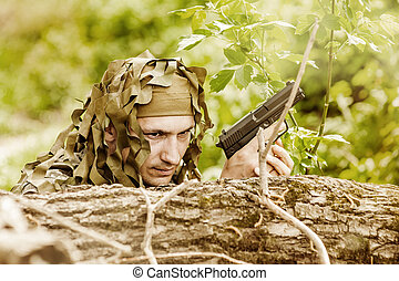 Young Camouflaged military man in forest with gun