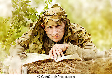 Military Camouflaged man in forest with black handgun...