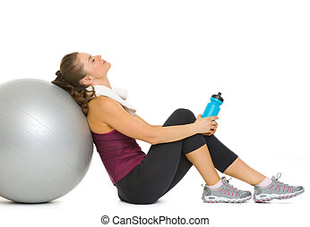 Tired fitness young woman relaxing after workout on fitness...
