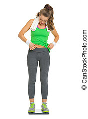 Fitness young woman checking body fat while standing on...