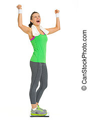 Happy fitness young woman standing on scales and rejoicing...