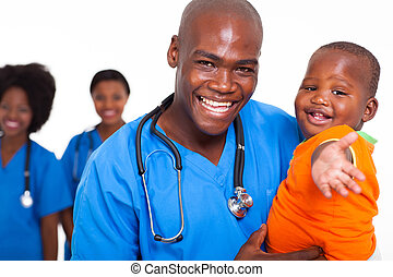 pediatric doctor playing with baby boy - african male...