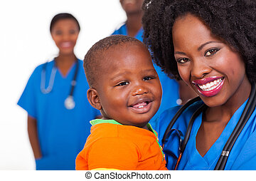 young african nurse carrying baby boy - happy young african...