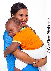 portrait of young african nurse carrying sleeping baby boy -...