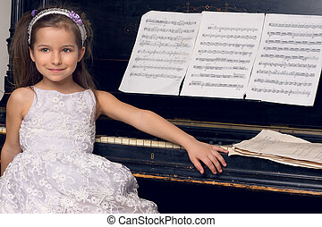 girl in a beautiful dress sits at the piano - little girl in...