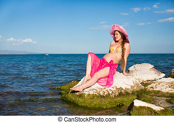 Happy beautiful pregnant woman in swimsuit relaxing at...