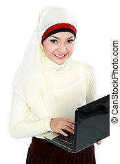 asian young muslim woman in head scarf using laptop