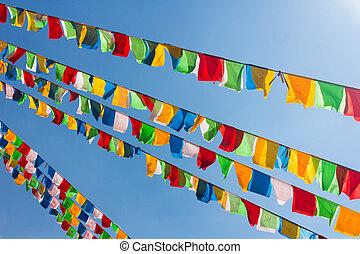 Buddhist tibetan prayer flags waving in the wind against...