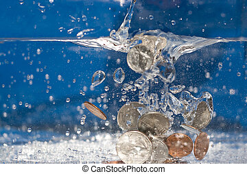 Money Down the Drain - A handful of coins dropping into a...