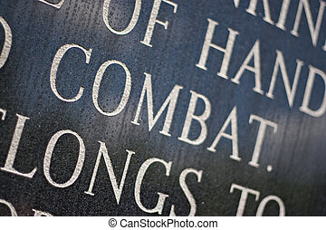 Combat - A closeup of the word COMBAT engraved on a war...
