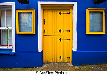 Yellow Door - Bright yellow dutch door on blue facade