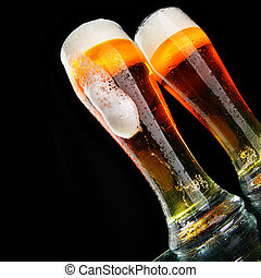 Beer - Glasses of beer with froth over black background