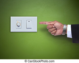 hand pointing to switch ofelectric appliance on green wall...