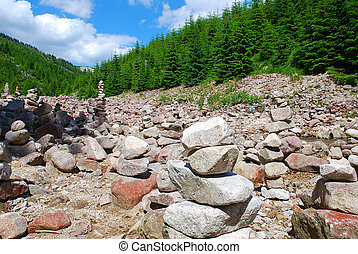 Stone cairns - stone cairn in mountain valleys in the spruce...