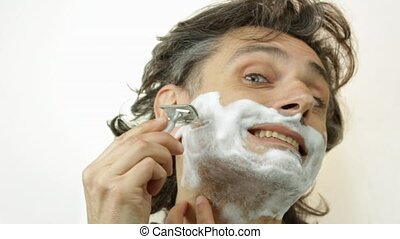 shaving with safety razor - Man shaving his cheek using...