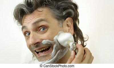 shaving cream face - cheerful man with shaving cream over...