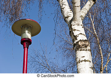 Ancient lamppost at parking of gasstation on highway -...