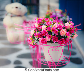 Artificial flower in vase with blurry doll in the background