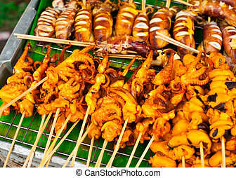 Traditional Thai food at market. Grilled seafood on sticks