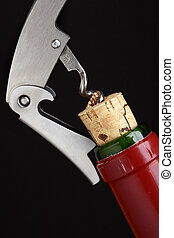Cork-screw opening wine bottle over black background