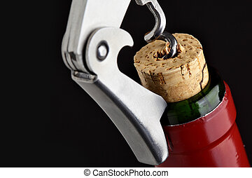 Cork-screw open wine bottle over black background