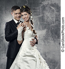 Wedding couple, bride and groom over gray grunge background