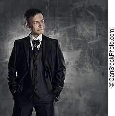 Handsome man in black suit. Wedding groom fashion. Gray...