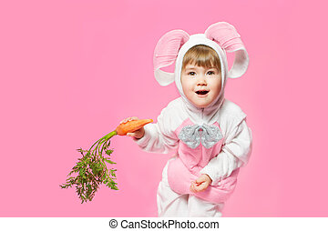 Child in bunny hare costume holding carrots. Pink background