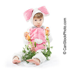 Child in bunny hare costume holding carrots. White...