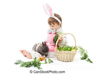 Child in bunny hare costume holding rabbit and carrot. White background