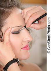 Photo session backstage: cosmetologist work with model