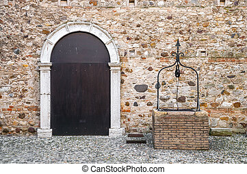 Stronghold front door on a stone wall with stony well
