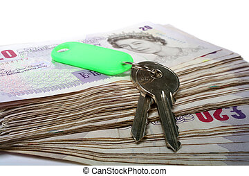 Money and keys - A set of house keys resting on a big pile...
