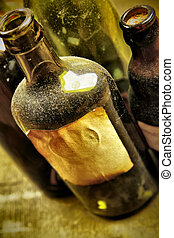 Old tagged bottles with transparent liquid close-up