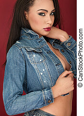 Seductive beautiful woman in a trendy denim top giving a...