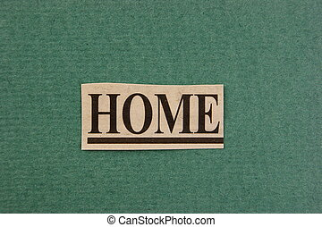 word home cut from newspaper on green background