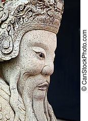 Ancient asian statue close-up over black gackground
