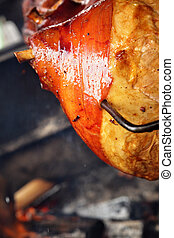 Grilled pig leg on spit close up
