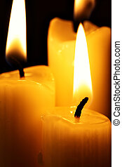 Burning candles - Three burning candles over a black...