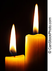 Two candles - Two burning candles over a black background