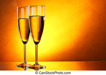 Champagne - Couple glasses of champagne over yellow...